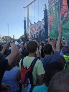 People Cheering at the National lead singer as he crowd surfs
